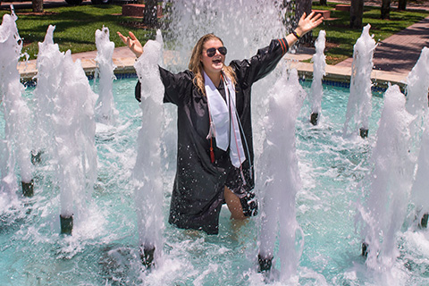 Student celebrating graduation in fountain